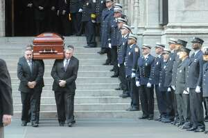 Stamford firefighters look on as the caskets are carried out at the end of the funeral for the three Badger sisters, Lilian, Sarah and Grace, at St. Thomas Church Fifth Avenue in Manhattan on Thursday, Jan. 5, 2012. The sisters were killed along with their grandparents, Lomer and Pauline Johnson, when their mother's Shippan home burned down on Christmas Day.