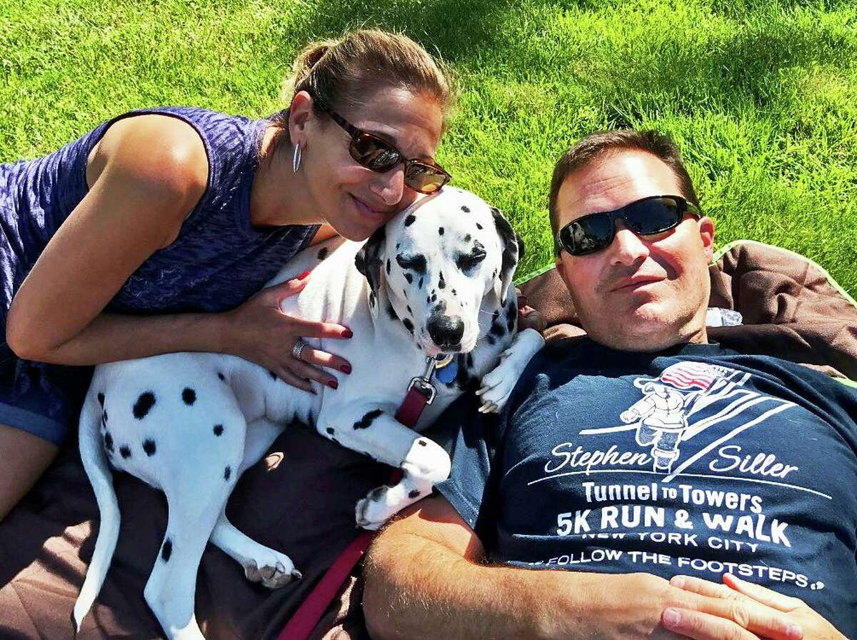 Fairfield County Trauma Response Team Board Member Dawn Roy, LCSW, and her husband, Jacques Roy of Stamford Fire and Rescue, with their dog, Lucky.
