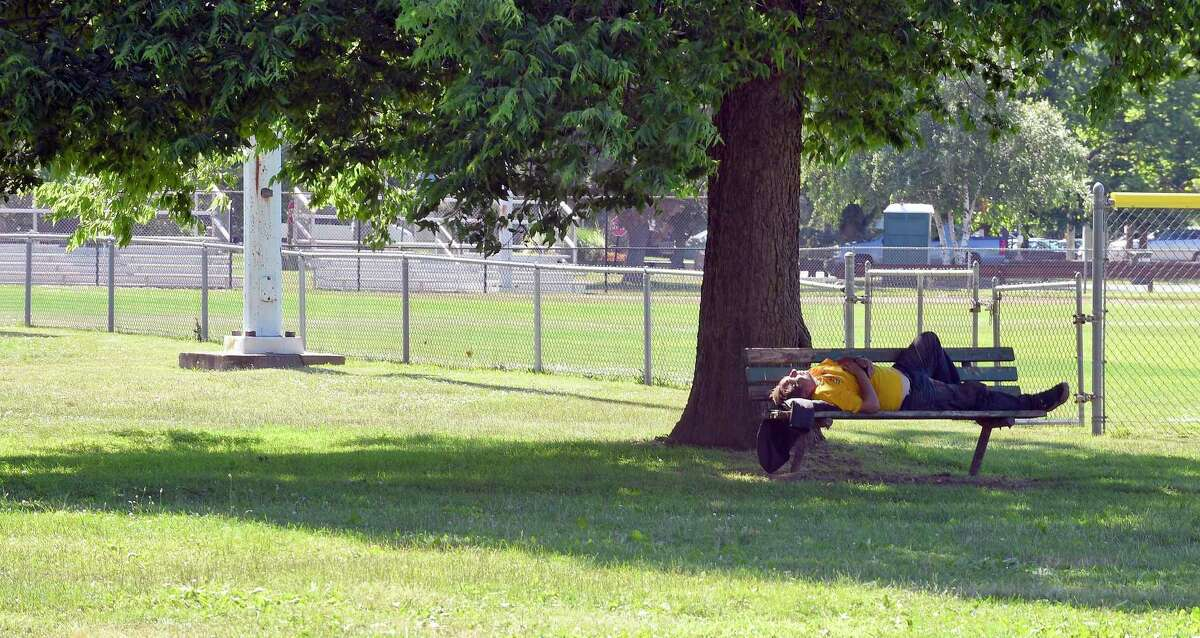 An individual finds a shady area on a park bench to nap at Cummings Park in Stamford, Conn. on June 19, 2018.