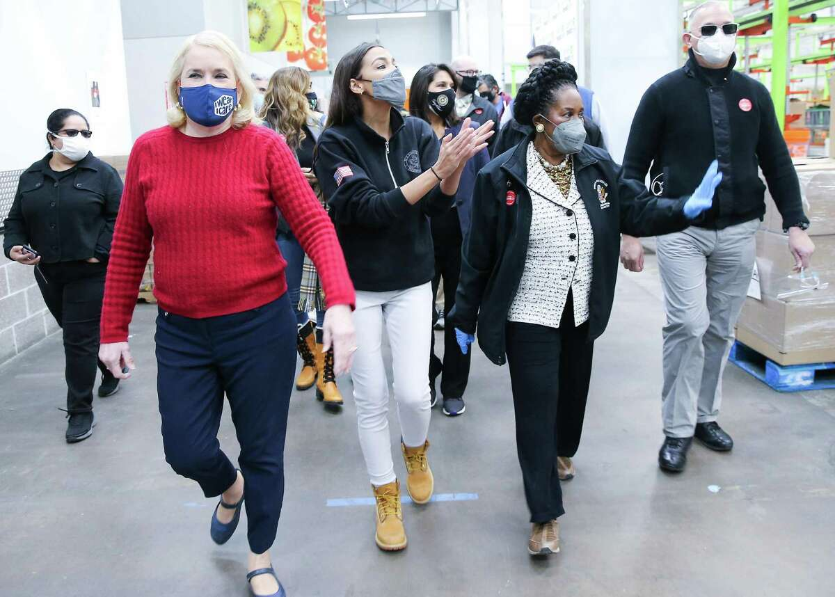U.S. Rep. Sylvia Garcia, from left, U.S. Rep. Alexandria Ocasio-Cortez and U.S. Rep. Sheila Jackson Lee wave to volunteers as they make their way to their work station at the Houston Food Bank on Saturday, Feb. 20, 2021.