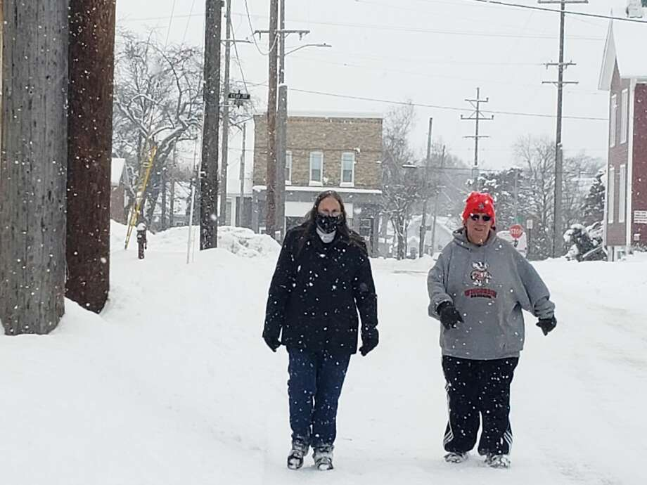 (From left) Sharon White and Lisa Fragomeli walk the snow-covered streets of Manistee to raise funds for assistance for people in Manistee County. Photo: Arielle Breen/News Advocate