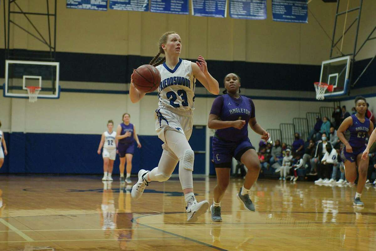 Friendswood's Ashlyn Ryall (23) glides to the basket past Angleton's Meshivia Mayberry (1) Friday at Friendswood High School.