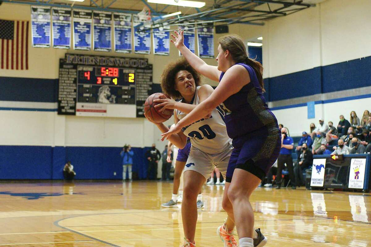 Friendswood's Rakel Hutchinson (30) tries to put up a shot over Angleton's Savanna Lopez (13) Friday in a recent playoff game. The Lady Mustangs were forced to end their season Tuesday because of COVID-19 issues.