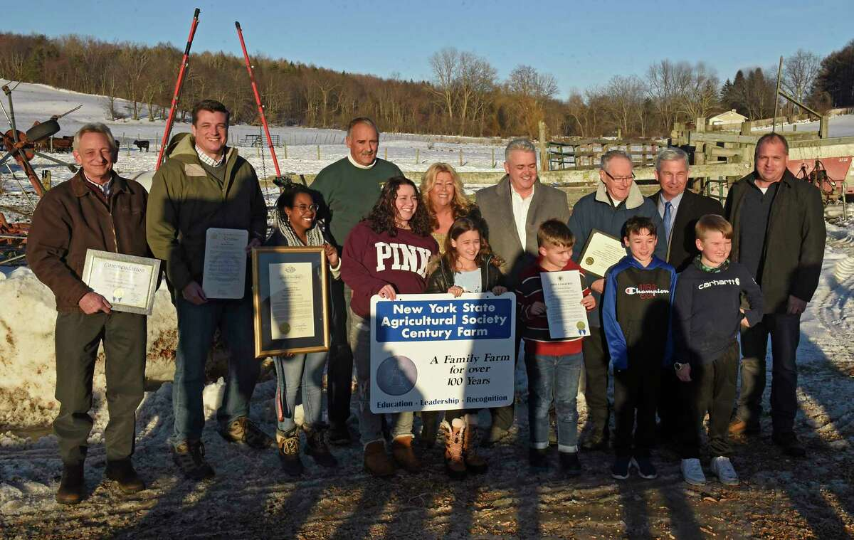 Bill Fogarty, fourth from left, and his wife Kathy, sixth from left, take a group photo with family and county officials after receiving the New York State Centennial Farm Award on behalf of the NYS Agriculture Society at the Fogarty dairy farm on Wednesday, Feb. 17, 2021 in Schaghticoke, N.Y. (Lori Van Buren/Times Union)
