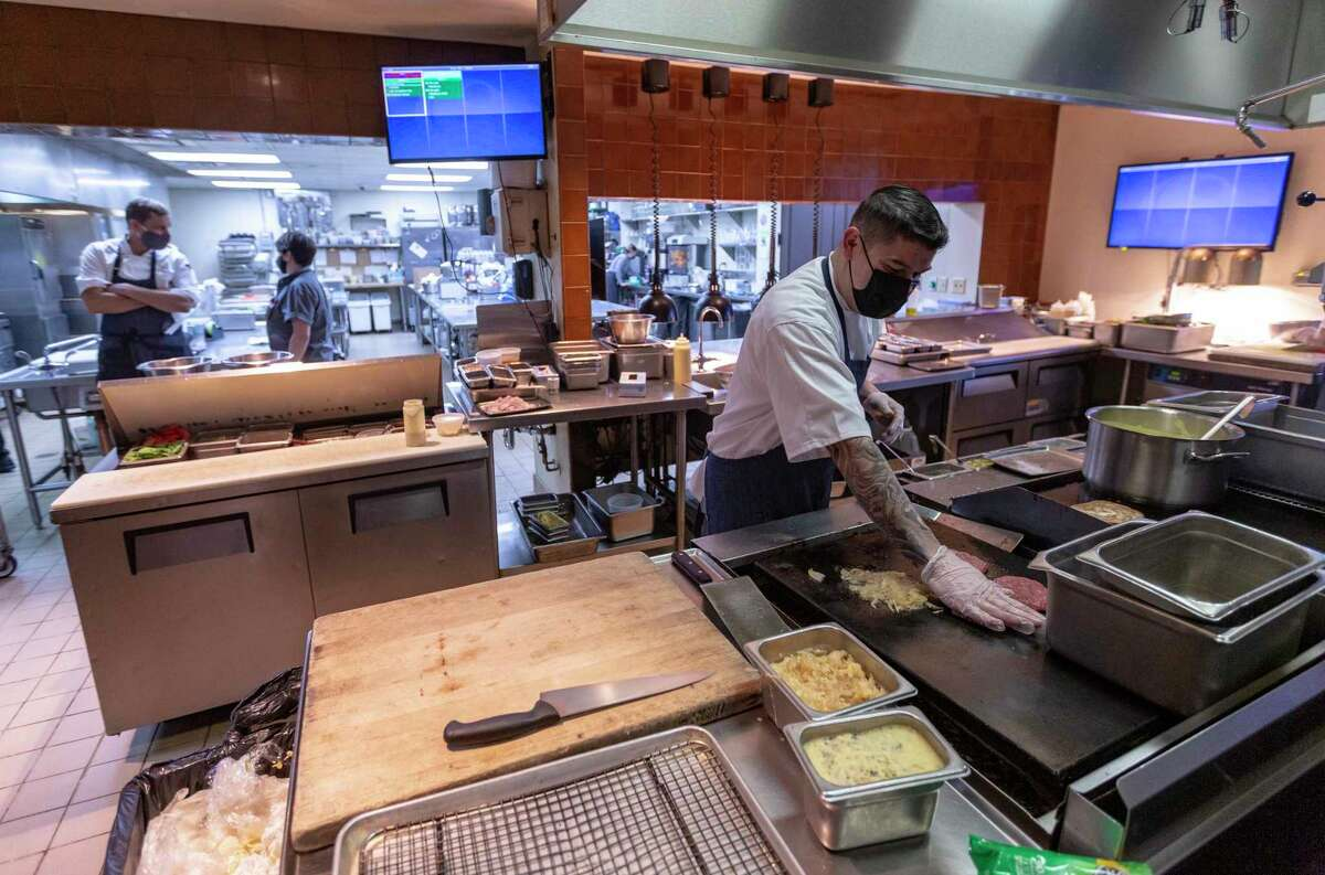 Executive chef Jaime Gonzalez prepares patty melt sandwiches Friday in the Hotel Emma kitchen. When the kitchen ran out hamburger buns, the burgers became patty melts.