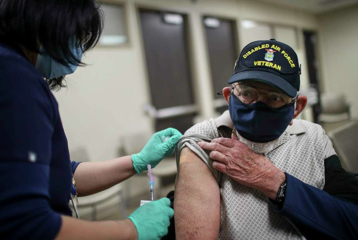 """Willie Adams, an Air Force veteran, gets his second vaccine shot from Yolanda DeLeon, a nurse, Saturday, Feb. 20, 2021, at Michael E. DeBakey VA Medical Center in Houston. """"Didn't bother me at all,"""" he said. """"I'm a tough old bird."""""""