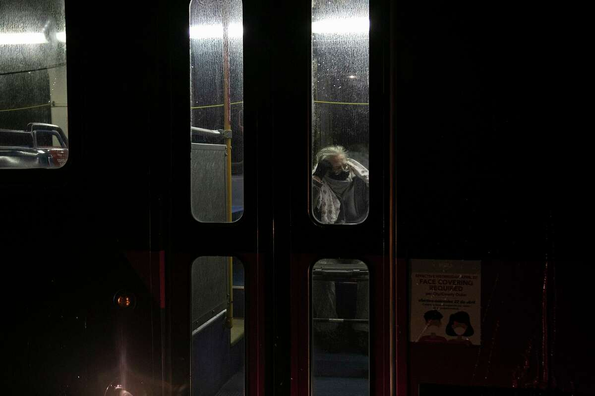 A Fair Avenue Apartments resident waits in a VIA bus for transport to the Grand Hyatt hotel downtown late Tuesday night after living without water and electricity since Sunday in San Antonio on Feb. 16, 2021.