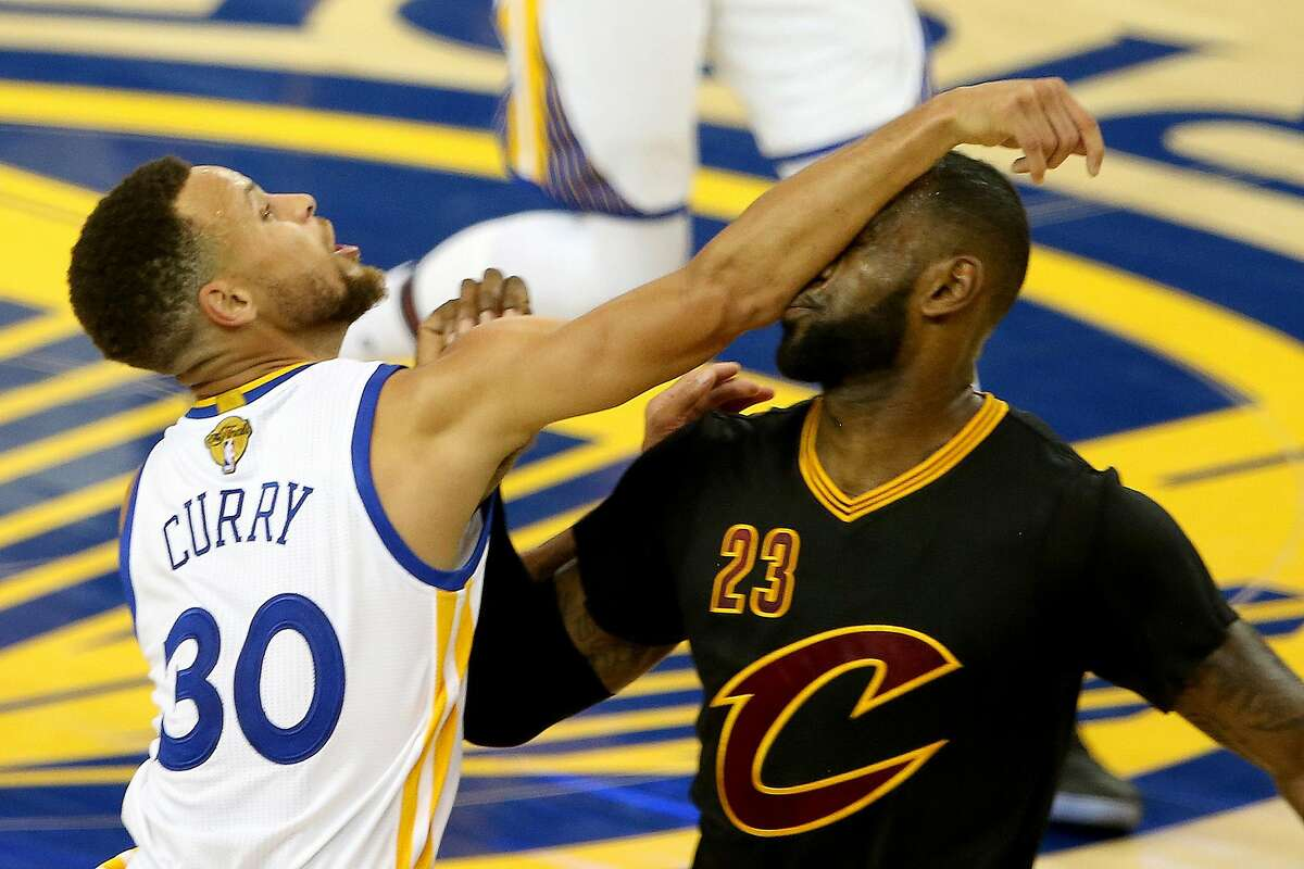 Golden State Warriors' Stephen Curry (30) follows his shot as he collides against the Cleveland Cavaliers' LeBron James (23) in the second quarter of Game 2 of the NBA Finals on Sunday, June 4, 2017 at Oracle Arena in Oakland, Calif. (Ray Chavez/Bay Area News Group/TNS)