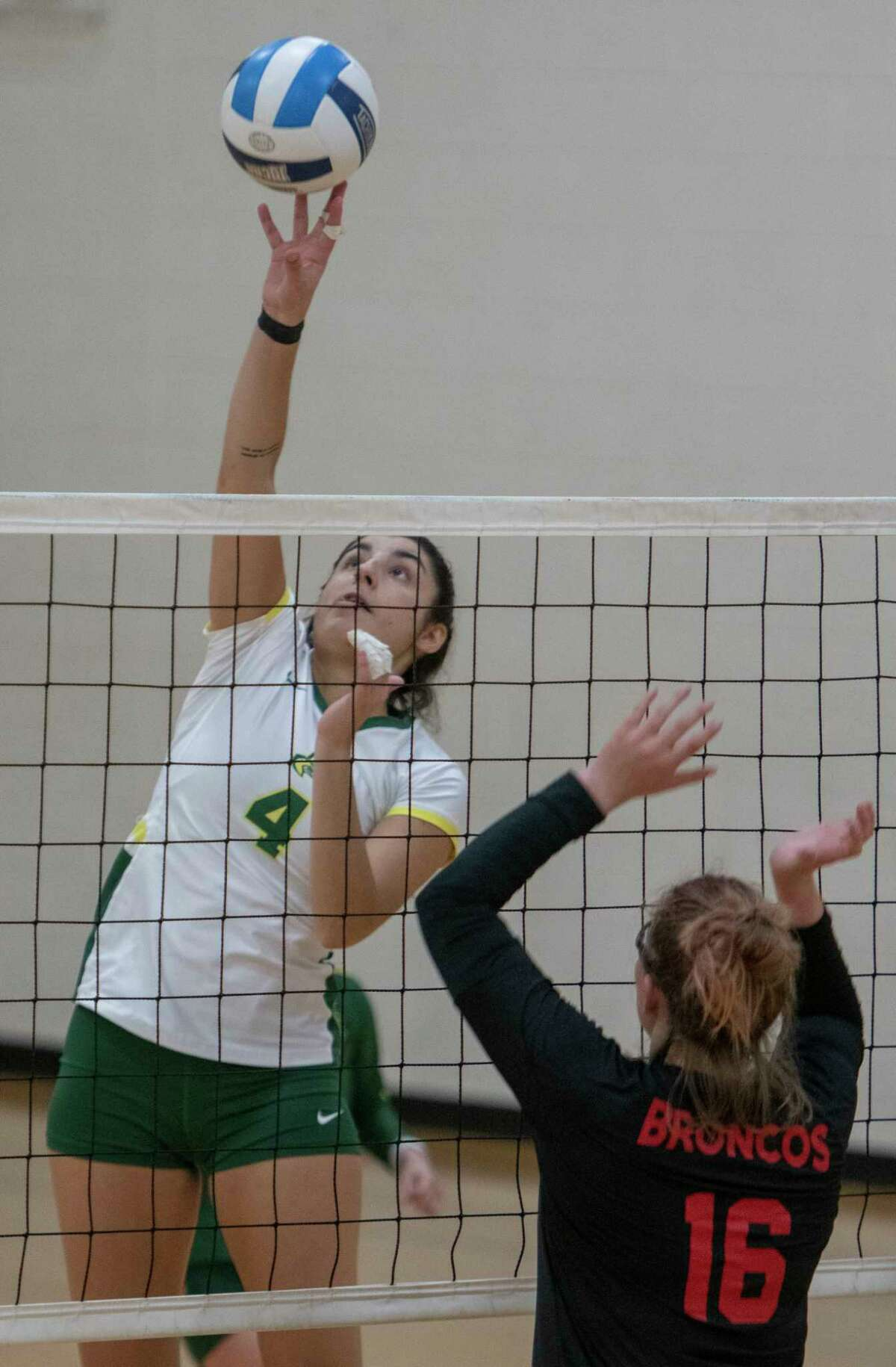 Midland College's Macarena Flores gets a quick tip over the net as NMMI's Darcy Dodd is late to block 02/20/2021 in the gym at Midland College Physical Education building. Tim Fischer/Reporter-Telegram