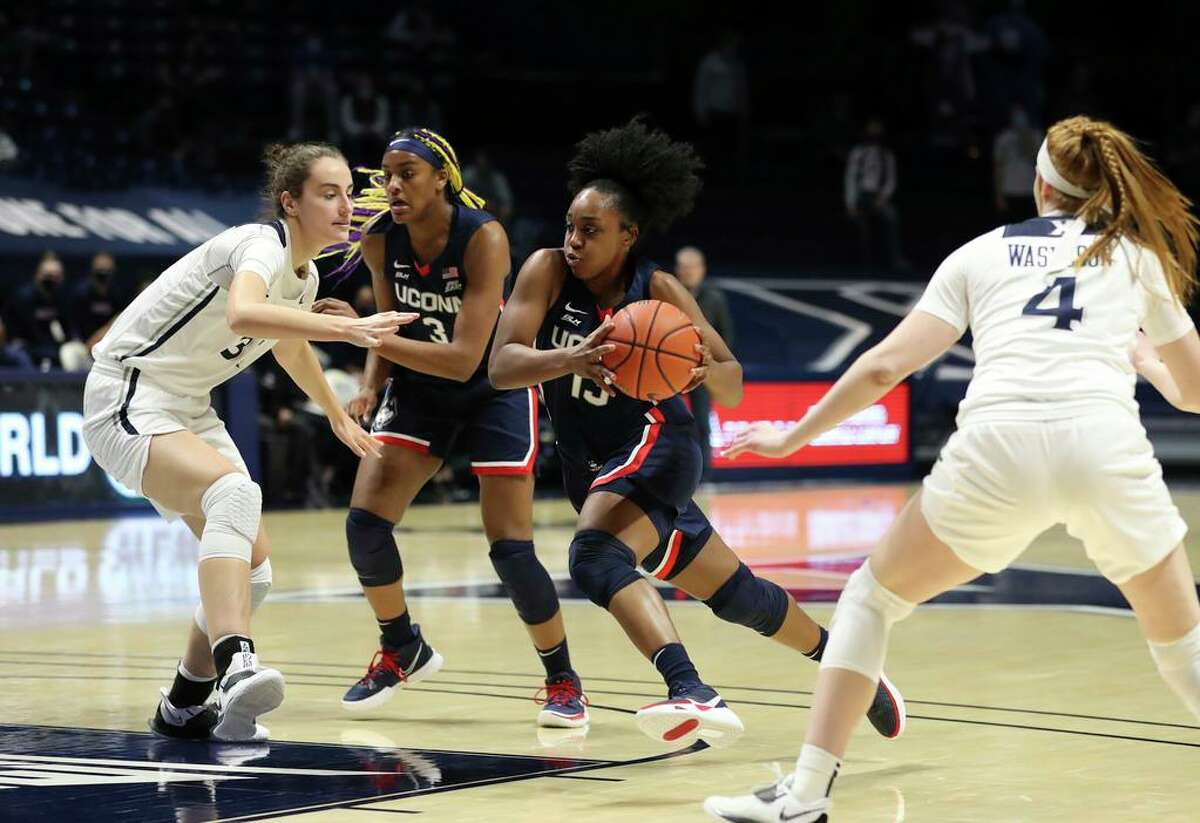 UConn guard Christyn Williams, center, drives to the basket against Xavier center Megan Harkey, left, and guard Lauren Wasylson (4) during the first half on Saturday.