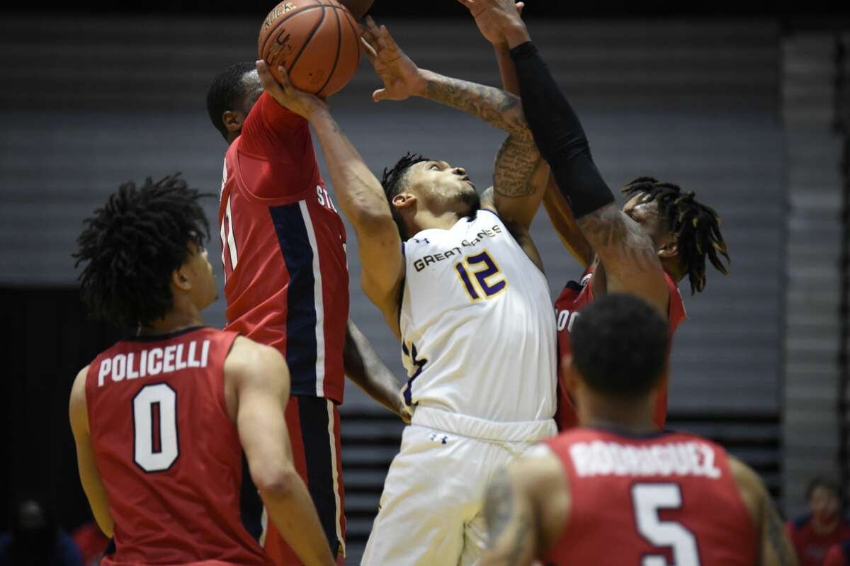 UAlbany foward Kellon Taylor is surrounded by Stony Brook defenders Saturday, Feb. 20, 2021, in an America East basketball game at SEFCU Arena. (Kathleen Helman/UAlbany Athletics)