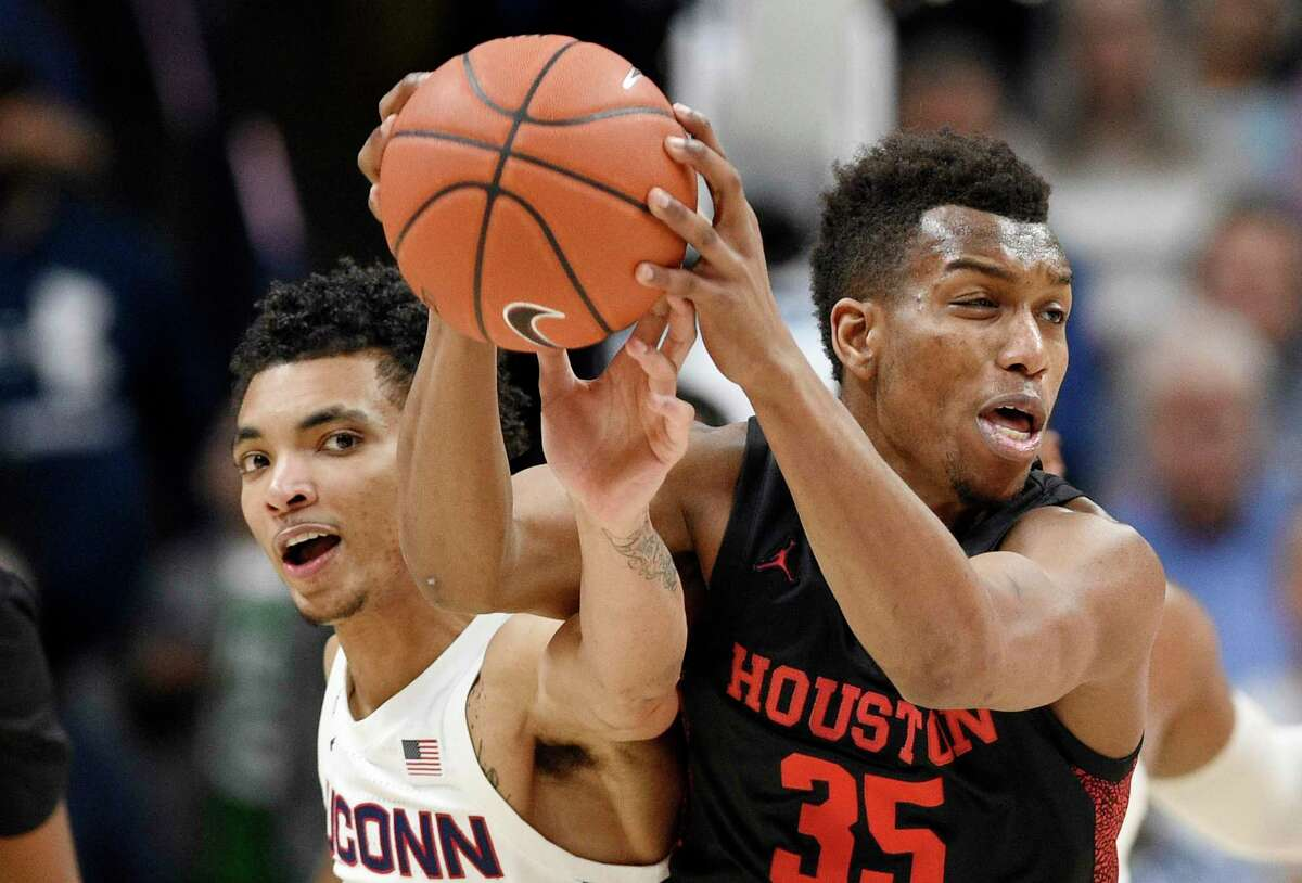 Connecticut's James Bouknight, left, reaches in and pressures Houston's Fabian White Jr. in the first half during a game on March 5, 2020.