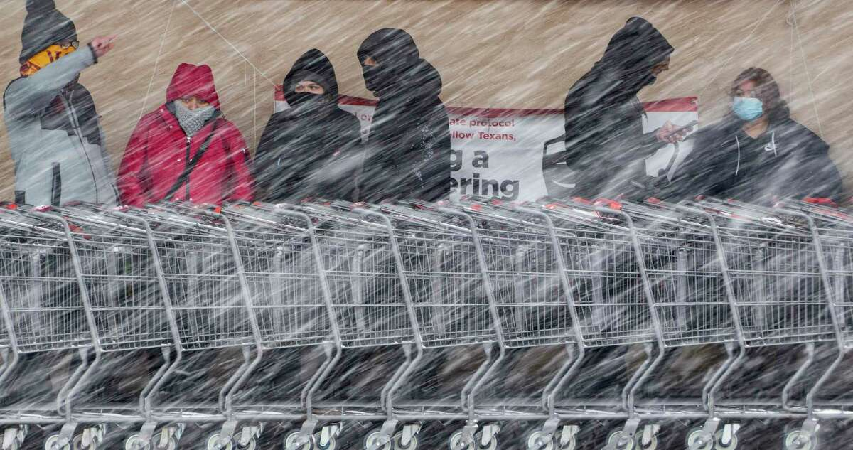 People wait in line to enter the H-E-B at West Avenue and Blanco Road as a brisk snow falls Thursday morning.