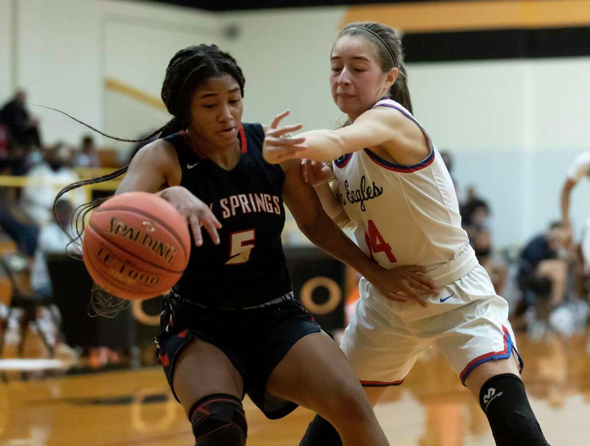Oak Ridge point guard Kylie Weeks (14) pushes the ball out of Cypress Springs point guard Alexis Howard's (5) control during the fourth quarter of a Region II-6A area round girls basketball game at Klein Oak High School, Saturday, Feb. 20, 2021 in Spring.