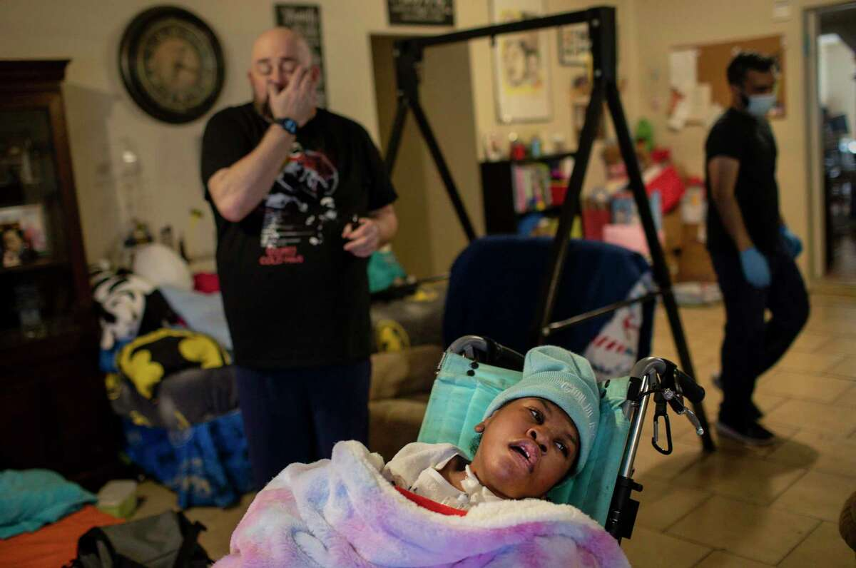 Hailey Cheevers, 10, sits in a chair in her living room as her father Stan, left, and Samir Haq, a home-health nurse, prepare the home following several days of winter storms Friday, Feb. 19, 2021, in Houston. Pipes broke in the cold weather causing parts of the ceilings to collapse.