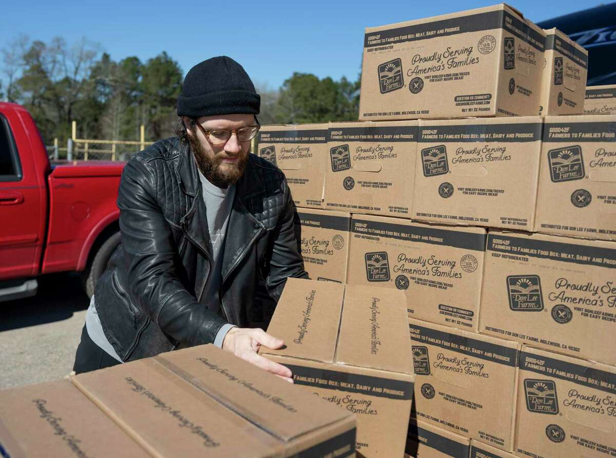Ryann Creglow with Vibrant Church handles boxed food during a distribution event held at Nelson Pool, Saturday, Feb. 20, 2021, in Splendora. The Dream Center partnered with Montgomery County and the Houston Food Bank to distribute fresh water and food to locals after an arctic storm caused widespread water insecurity in the state of Texas.