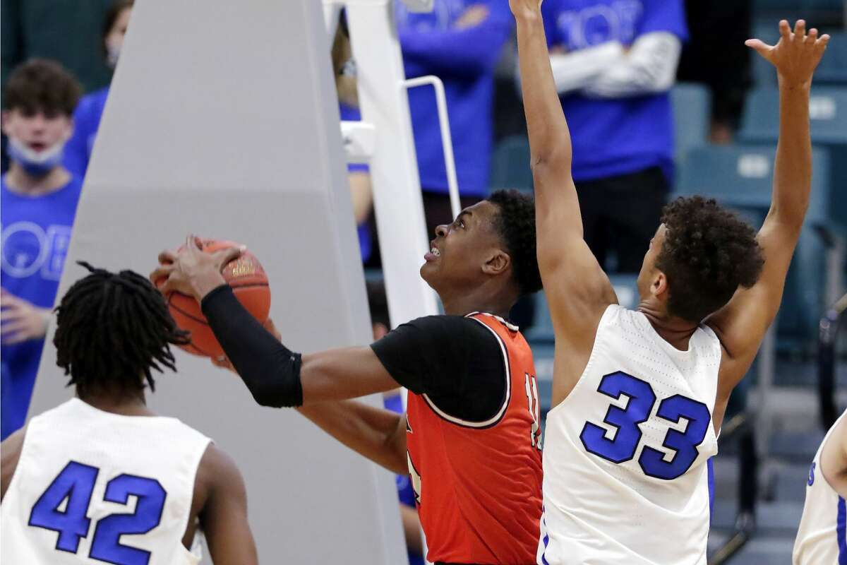 Bush's Tyler Smith, middle, puts up a shot between Katy Taylor's Troy Harris (42) and Elijah Melchiorre (33) during a 6A district boys high school basketball playoff game Saturday, Feb. 20, 2021 at the Merrell Center in Katy, TX.