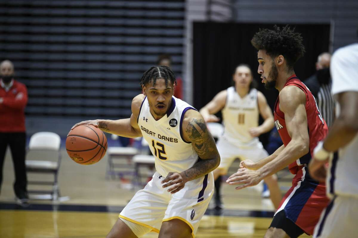 Kellon Taylor (12) looks to drive against Stony Brook defender Juan Felix Rodriguez in an America East basketball game Saturday, Feb. 20, 2021, at SEFCU Arena in Albany. With 13 points, Taylor was the Great Danes' only double-figure scorer in a 59-43 loss to the Seawolves. (Kathleen Helman/UAlbany Athletics)