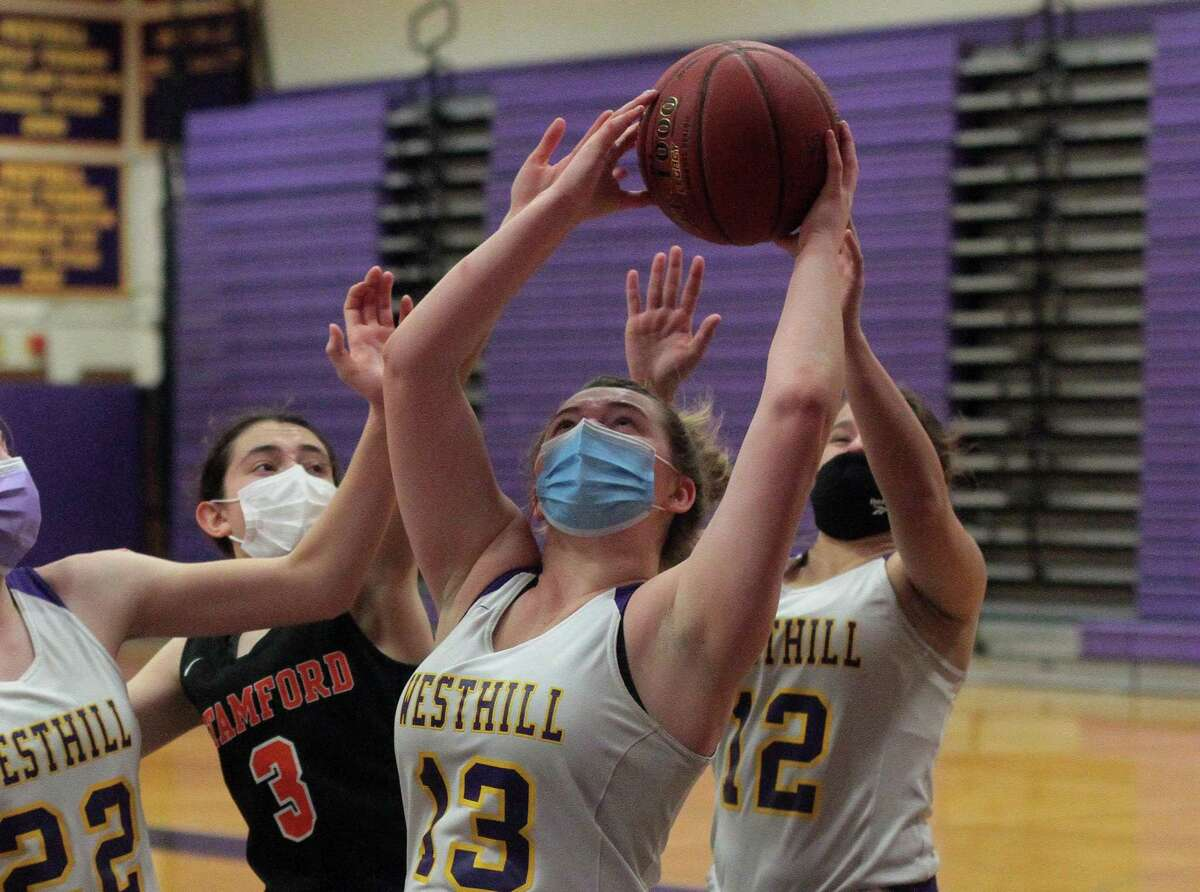 Westhill's Peyton Hackett (13) grabs a rebound during girls basketball action against Stamford in Stamford, Conn., on Saturday Feb. 20, 2021.