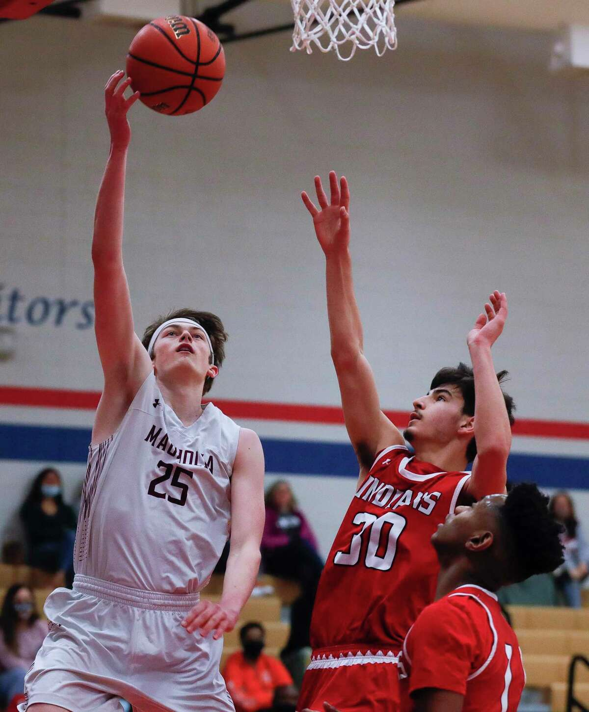 Magnolia guard Kyler Fuller (25) shoots past Cleveland guard Jonathan Aguilar (30) during the first quarter of a Region III-5A area bi-district basketball playoff game at Oak Ridge High School, Saturday, Feb. 20, 2021.