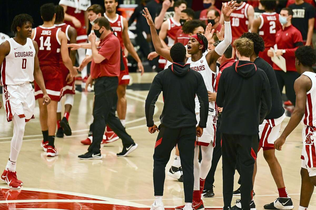 Washington State guard Noah Williams (center) is surrounded by teammates after scoring a 3-pointer to tie the game at the end of the second half. The Cougars won after three overtimes.