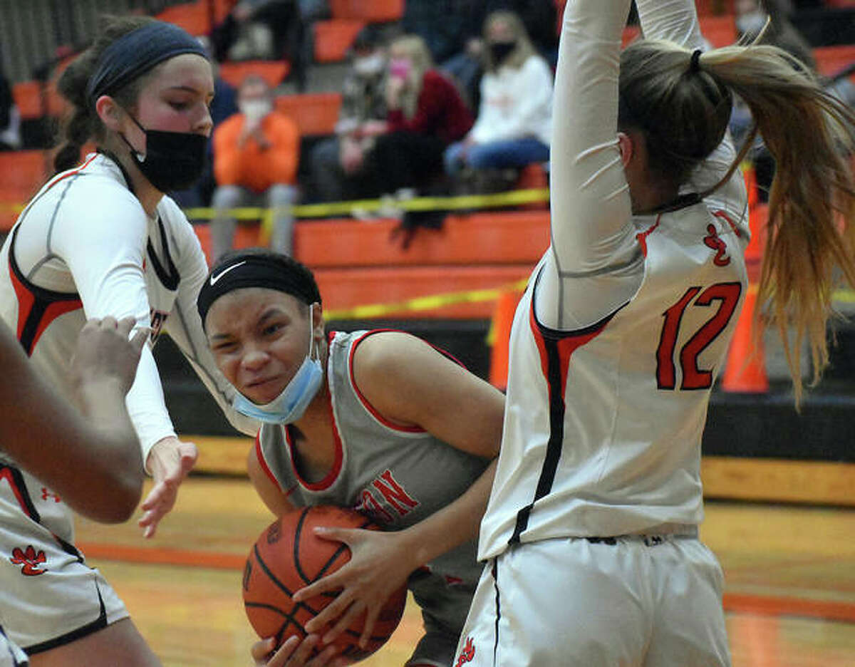 Alton's Khalyah Goree tries to split EHS defenders Elle Evans, right, and Ella Cook in the third quarter of Saturday's game in Edwardsville.