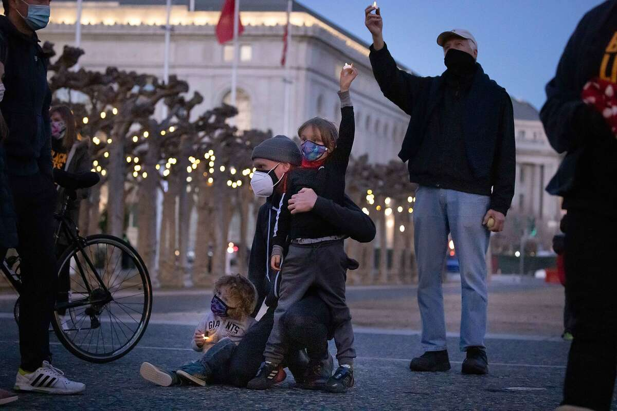 Felix Lang, 2, father Nick, and Xavier, 6, attend a candlelight vigil near City Hall on Saturday in support of teachers' reopening plan.
