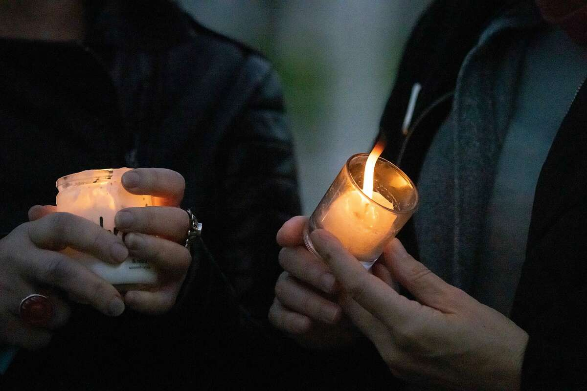 Cynthia Lasden and Liz Kimbal hold candles at a vigil in support of teachers at Civic Center Plaza on Saturday.
