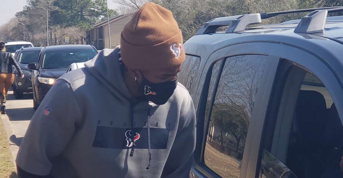 Texans' Jacob Martin passed out vegetables, canned goods and milk to families in need at Harvest Time Church on Saturday.