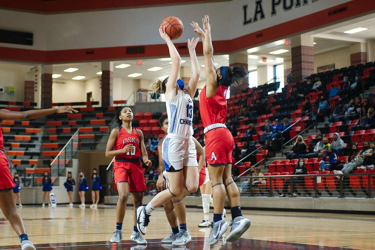 Clear Springs' Kenna Gibson (13) tries to put up a shot over Atascocita's Blake Matthews (1) Saturday, Feb. 20 at La Porte High School.