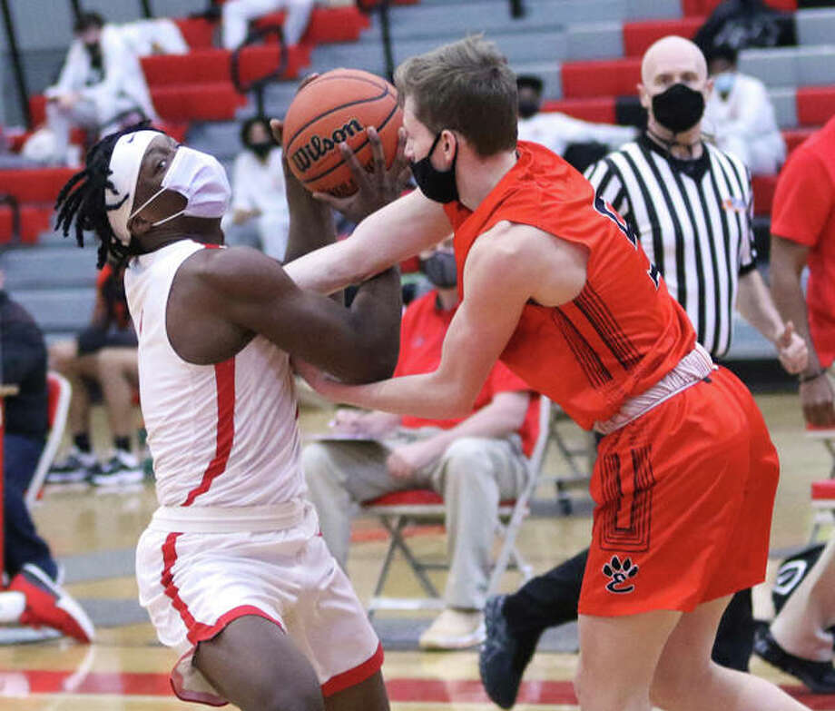 Alton's Ja'Markus Gary (left) is fouled by Edwardsville's Preston Weaver to prevent a layup on a Redbirds' fastbreak in the second half Saturday at Alton High in Godfrey. Photo: Greg Shashack / The Telegraph