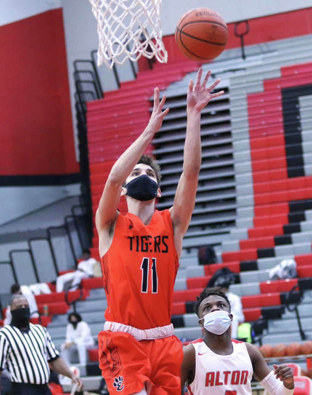 Edwardsville's Brennan Weller (11) scores two of his 30 points while Alton's Keith Smith watches the play Saturday at Alton High in Godfrey. Weller scored 30 points in the Tigers' win to become Edwardsville's 24th player to score more than 1,000 points in his career.