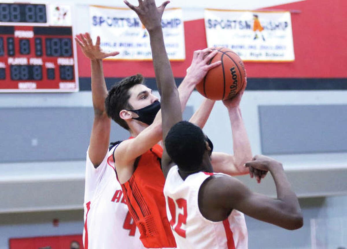 Edwardsville's Brennan Weller puts up a shot between Alton's Kyle Hubbard (12) and Lathan O'Quinn during the first half Saturday at Alton High in Godfrey. Weller scored 30 points in the Tigers' win to go past 1,000 for his career.