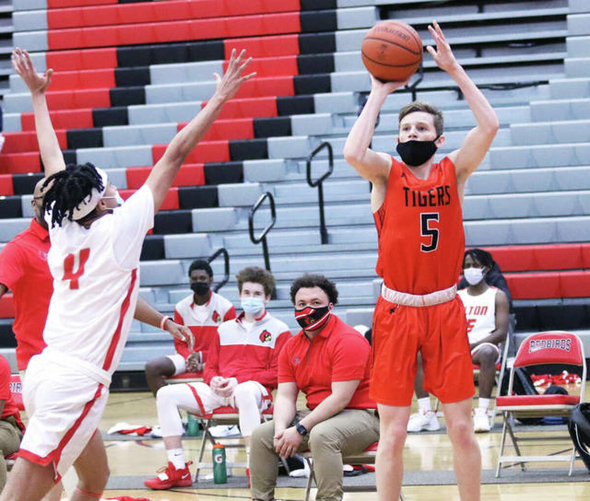 Edwardsville's Preston Weaver (5) hits the first of his four 3-pointers as Alton's Lathan O'Quinn arrives too late disrupt contest the shot in the second quarter Saturday at Alton High in Godfrey.