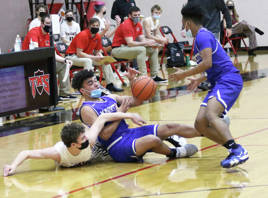 Marquette Catholic's Davin Thompson (middle) wins the loose ball from Triad's McGrady Noyes and passes to the Explorers' Cortez Harris in the second half Saturday in Troy. Photo: Greg Shashack / The Telegraph