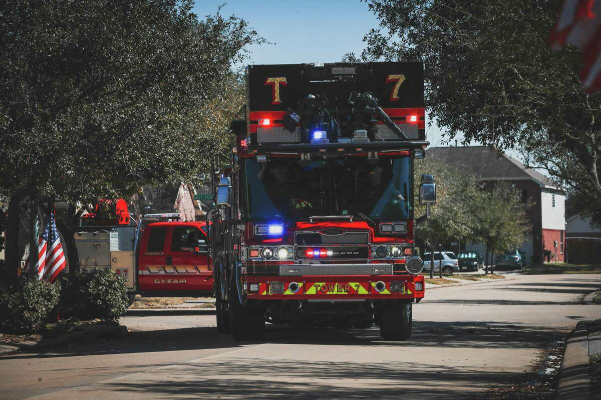 The imposing Tower 8 ladder truck makes the turn as the parade gets underway in the 10800 block of 10871 W. Lime Blossom Court in Cypress, Texas on Saturday morning. The crew was aboard to salute the 100th birthday of 100-year-old Cyril Bell.
