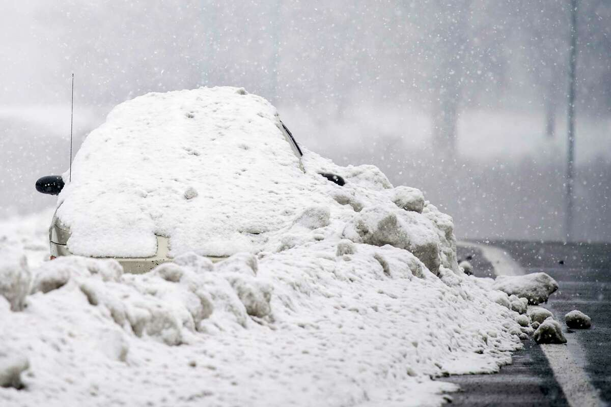 An abandoned car is covered in snow on the shoulder of Briley Parkway in Nashville, Tenn., Thursday, Feb. 18, 2021. (Andrew Nelles/The Tennessean via AP)
