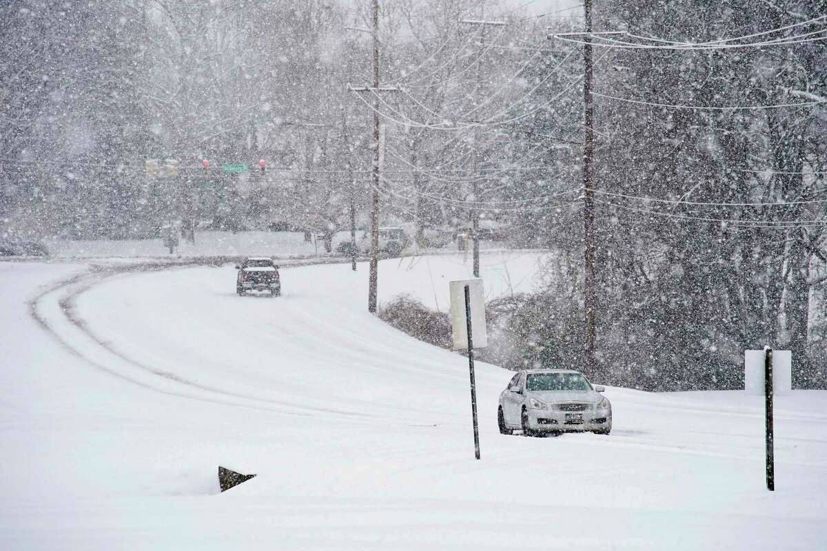 Vehicles drive along Two Rivers Parkway as snow falls in Nashville, Tenn., Thursday, Feb. 18, 2021. (Andrew Nelles/The Tennessean via AP)