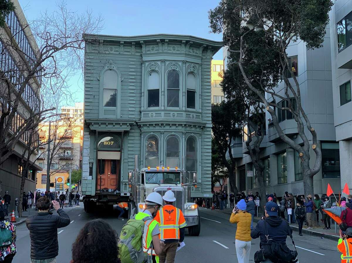 A crowd follows a Victorian home as it parades the wrong way down the street to its new home at a top speed of 1 mph. It was the first time such a home was relocated in S.F. in 50 years.