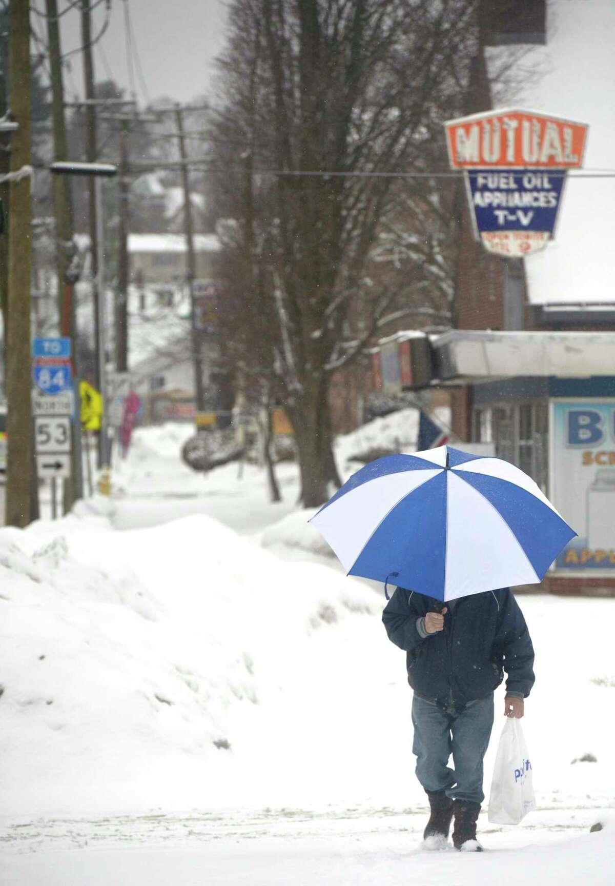 John Dlugozima, of Danbury, walks home from the store during Thursdays snow storm. February 18, 2021, in Danbury, Conn.