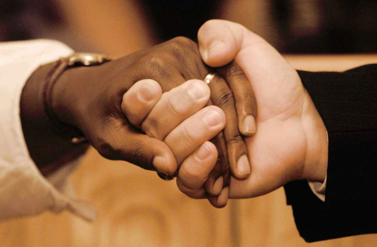 Two people hold hands in the United States during a previous year. The non-organization, Stand Together Against Racism, (S.T.A.R), in New Canaan, is offering a six session workshop series titled