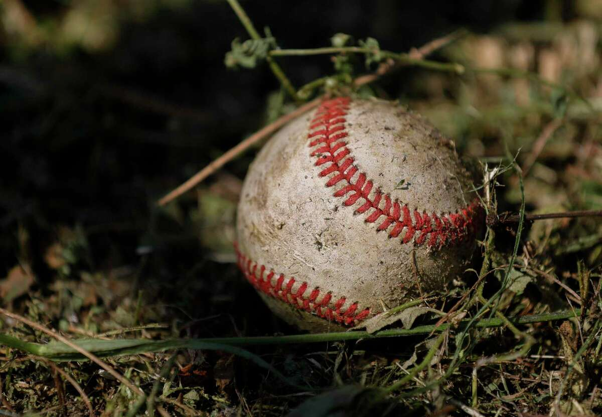 A baseball is seen in the grass behind the outfield fence at Oak Ridge High School, Tuesday, May 19, 2020, in Oak Ridge.