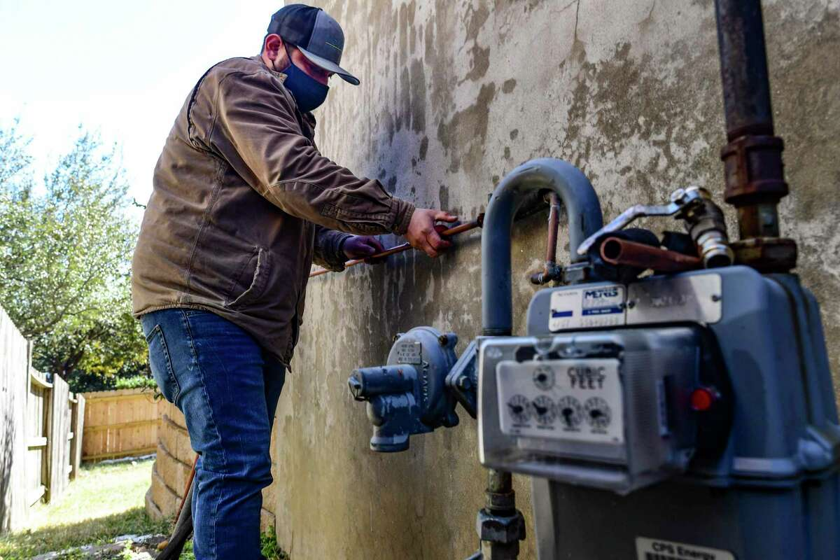 Plumber Alex Ortega of Beyer Boys works on rupture pipes on a home in the Stone Oak area of the city on Friday. The recent subfreezing temperatures across Texas caused many pipes to burst.