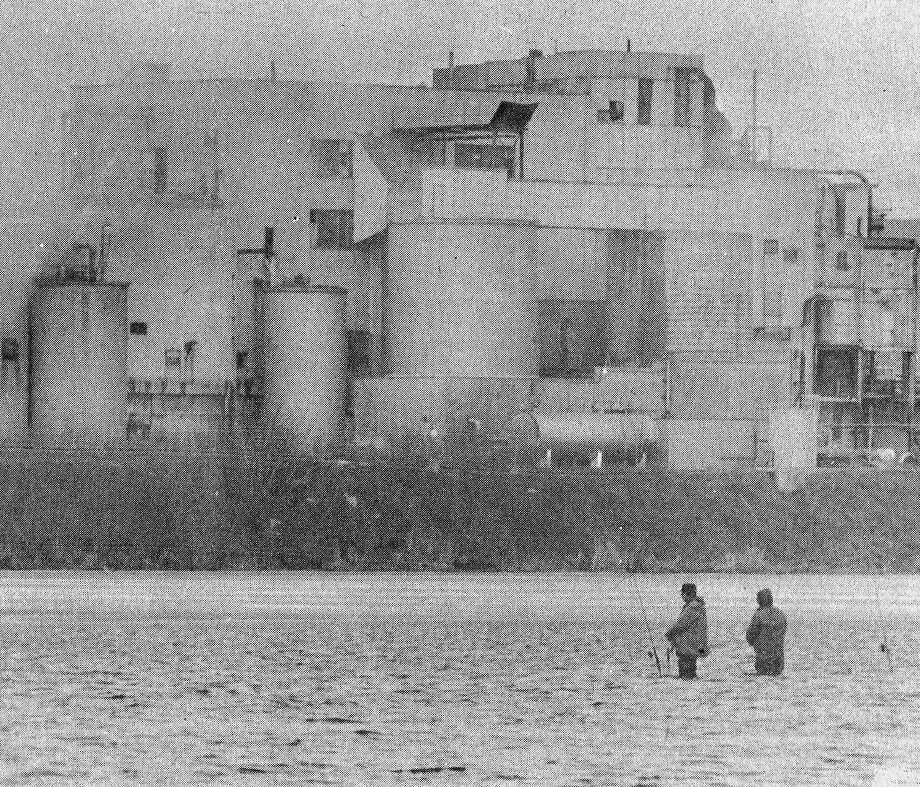 From the front page of the News Advocate on this day in 1981, two fishermen stand beneath the shadow of the Packaging Corporation of America, trying their fishing luck in Manistee Lake this morning. Ice shanties clustered on the shores, and waders were the order of the day as the two stood on a sand bar near the mouth of the Little Manistee River.(Manistee County Historical Museum photo)