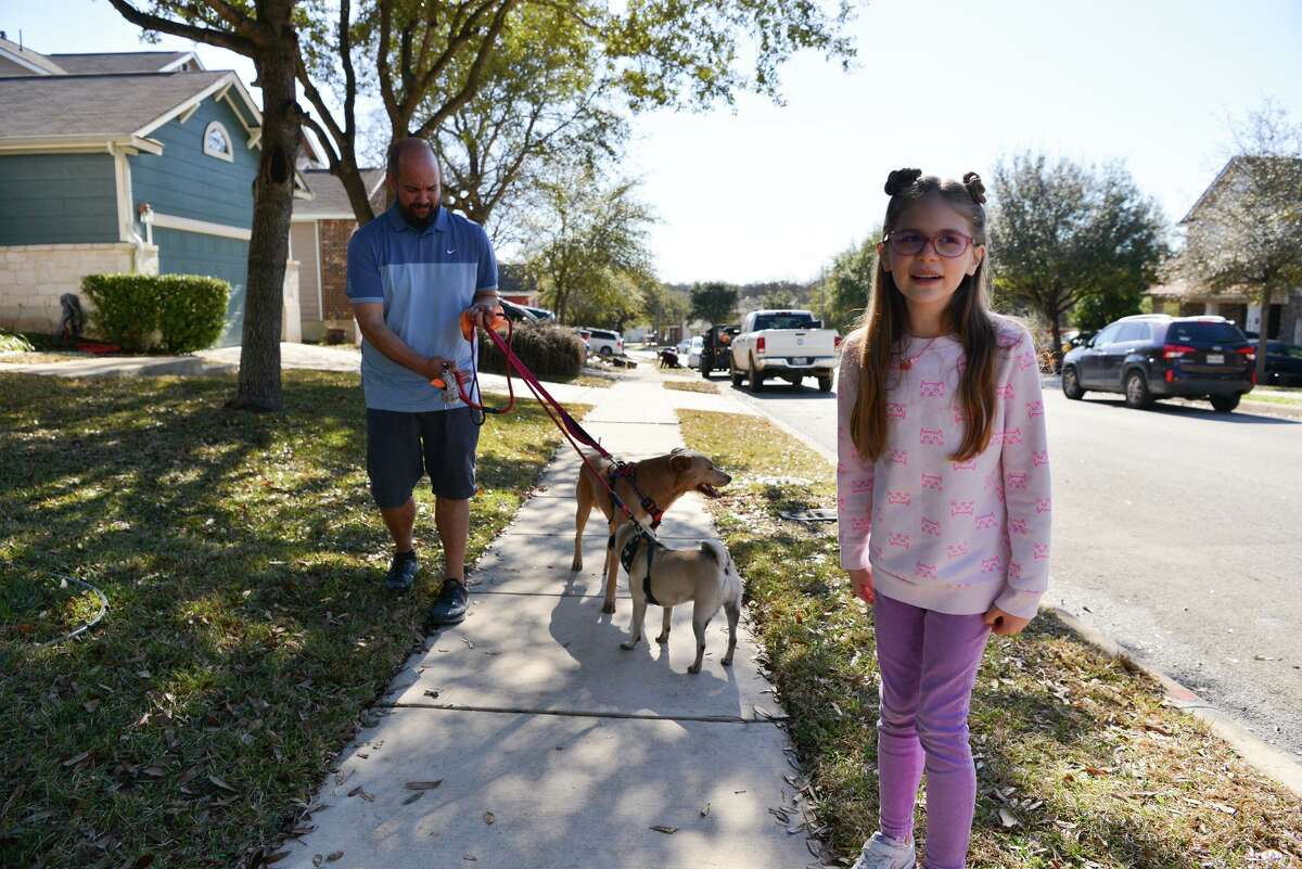 Charlotte Hartman, 8, talks with a visitor as her father, Michael, holds the family dogs in their Southwest Side neighborhood. Neighbors seek out Charlotte to help them find lost or missing pets.