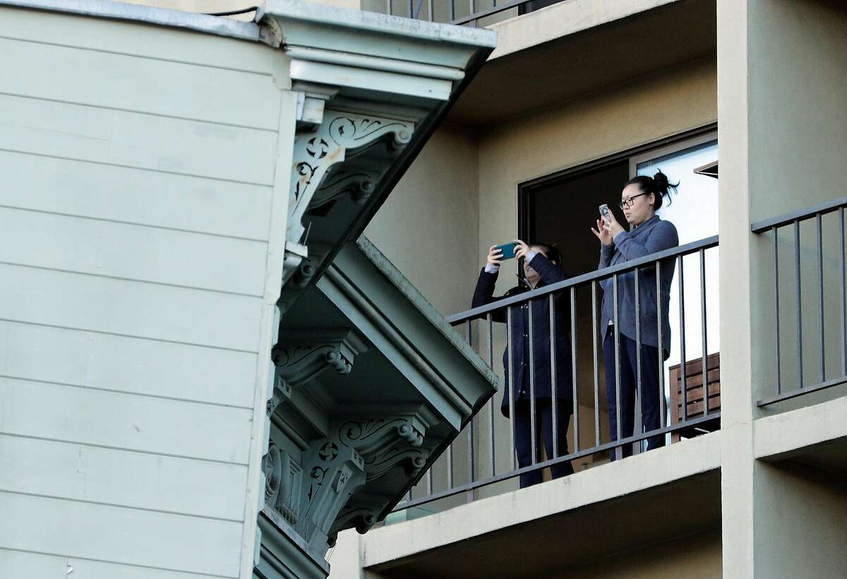 Two neighbors takes photos from their balcony as the two-story Victorian home leans nearby while it was relocated from 807 Franklin Street to 635 Fulton Street in San Francisco, Calif., on Sunday, February 21, 2021. The house, known as the Englander House, which was built in 1882, was a historic home and the owner spent years preparing for the move.