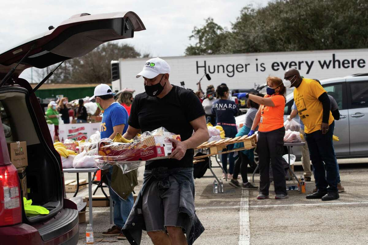 Houston Food Bank employee Enrique Albi, 50, approaches a vehicle to load food during a food distribution event in the aftermath of a freeze that left the Houston area depleted of resources, Sunday, Feb. 21, 2021, in Houston.