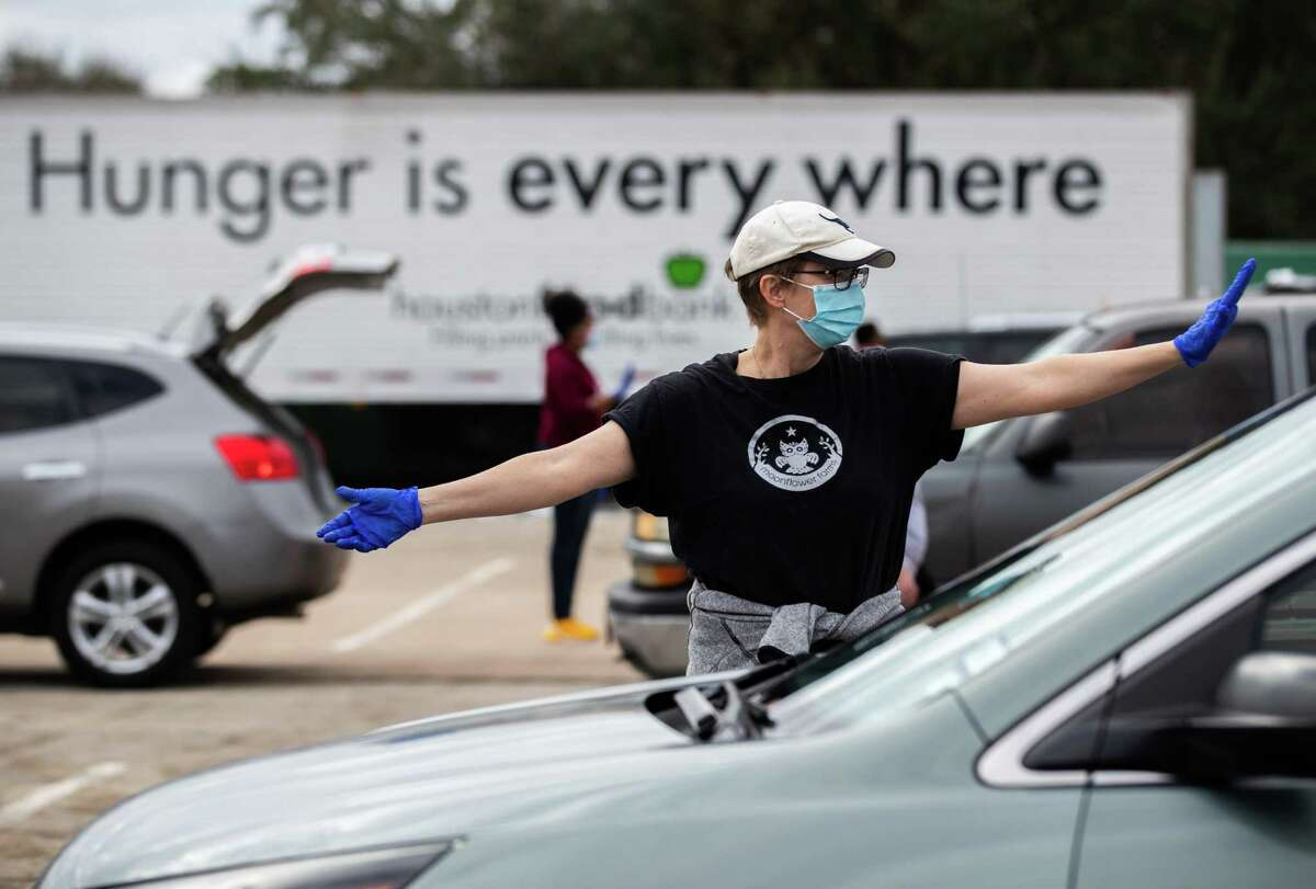 Houston Food Bank volunteer Cecilie Tindlund, directs traffic during a food distribution event at NRG Park, Sunday, Feb. 21, 2021, in Houston.