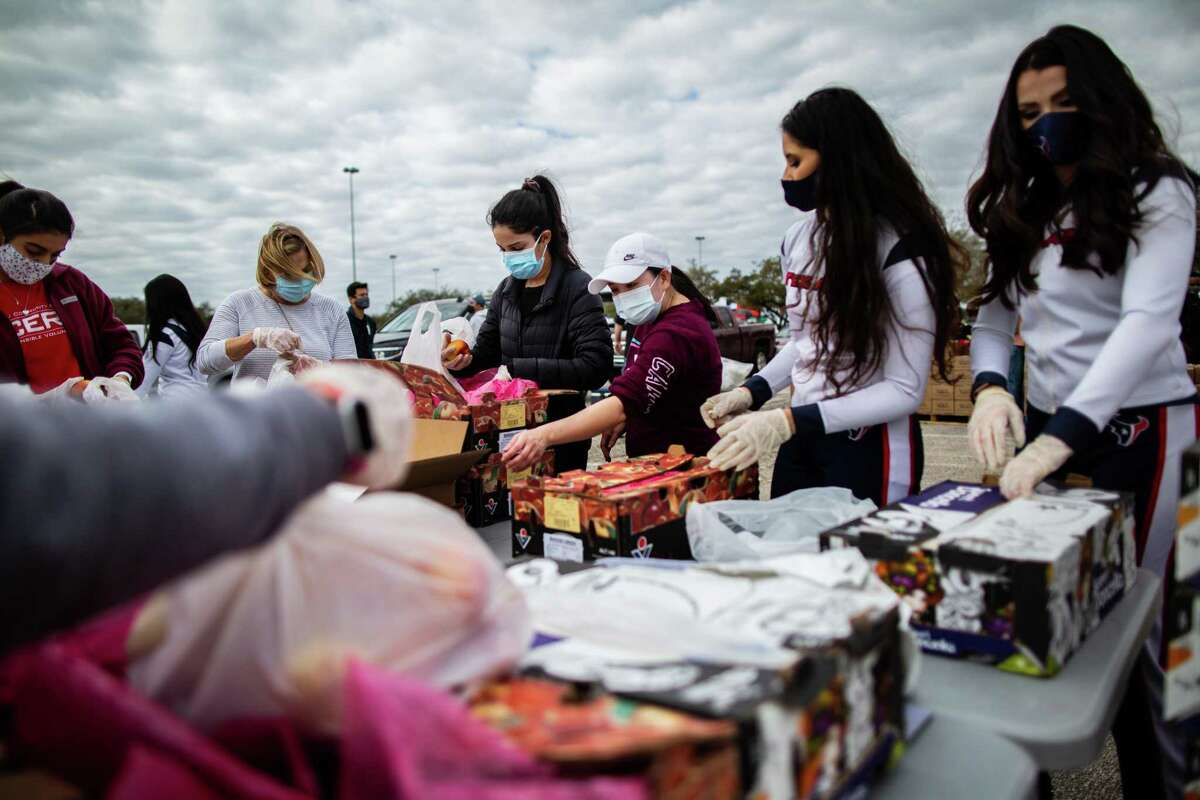 Texans Cheerleaders and other volunteers pack food to distribute to hundreds people picking supplies from their cars after a freeze that left the Houston area depleted of resources, Sunday, Feb. 21, 2021, in Houston.