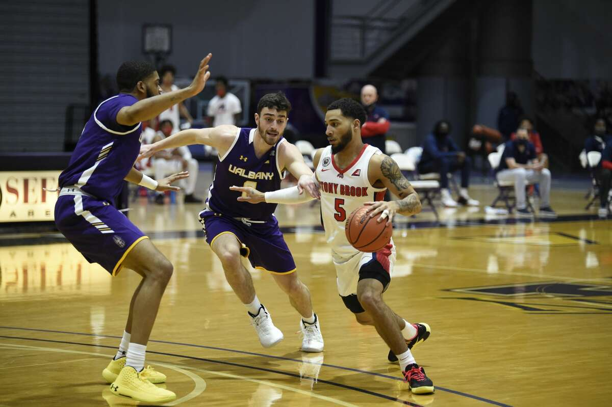 Stony Brook guard Juan Felix Rodriguez tries to get past UAlbany defenders Jarvis Doles, left, and Antonio Rizzuto in an America East basketball game Sunday, Feb. 22, 2021, at SEFCU Arena in Albany. UAlbany defeated Stony Brook 67-59 in the regular-season finale for both teams. (Kathleen Helman/UAlbany athletics)
